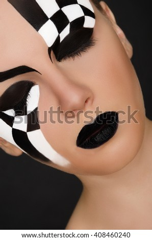 face of young woman with black and white pattern on black background - stock photo