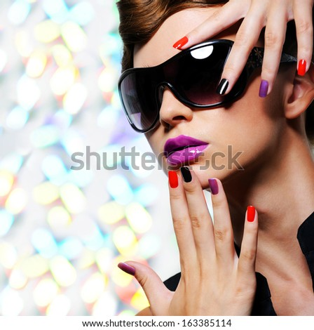 Face of young woman with  fashion manicure and black sunglasses - stock photo