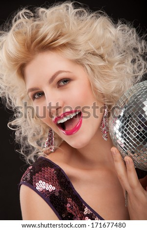 face of young woman with fashionable make-up and disco ball in hands