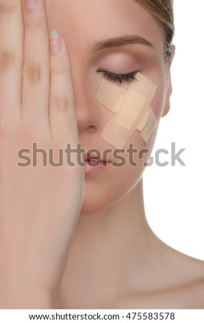 face of young woman with medical patch isolated on white