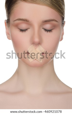 face of young woman with plaster on her lips isolated on white