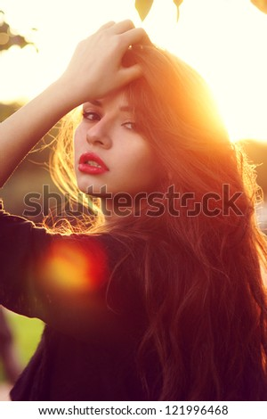 face outdoor portrait of young beautiful tender girl lightened with sun backlit - stock photo