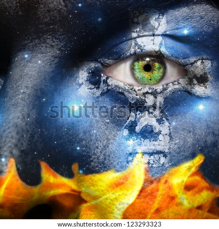 Face overlay of the seven sisters constellation with a Celtic cross centering around the green eye with a base of fire flames