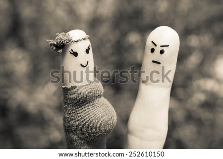 Face painted on fingers. The man was upset because the woman is pregnant. Black and white shot.  - stock photo