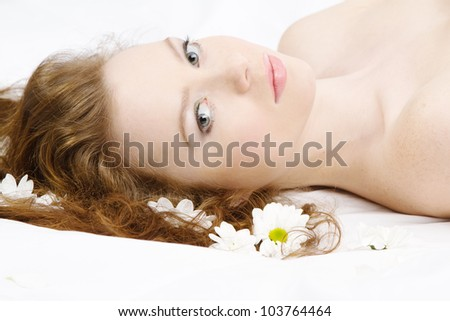 Face portrait of a beautiful model with flowers, studio photo - stock photo