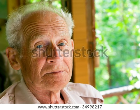 face portrait of a serious senior man - stock photo