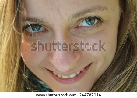 Face portrait of a young, smiling, blond woman looking at camera, outdoor