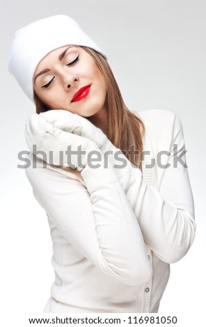 Face portrait of a young woman in white knit wool  hat and mittens - stock photo
