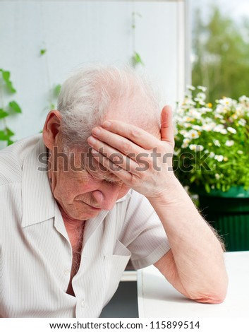 face portrait of an old senior man, he has a headache, his hand on his forehead - stock photo