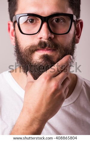 Face portrait of bearded man in glasses with hand on beard against white background