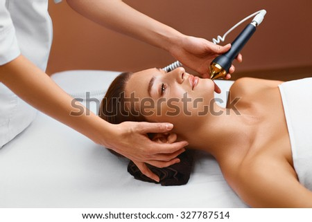 Face skin care treatment. Ultrasound cavitation face care procedure in medical beauty cosmetology spa center. Beautician applying regenerative, rejuvenating, moisturizing, anti-aging cosmetics on skin - stock photo