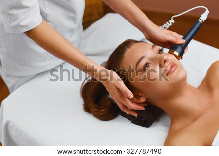 Face skin care.  Woman lies on a table in a medical beauty cosmetology spa salon getting facial skin care treatment. Ultrasound cavitation anti-aging, rejuvenation, lifting procedure. Beauty concept - stock photo