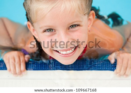 face smiling little girl in the pool close up