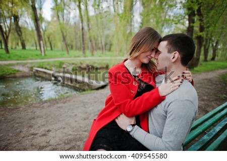 Face to face of lovely couple sitting on bench at park - stock photo