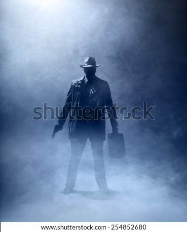 Faceles man with a gun and a briefcase standing in the fog. - stock photo