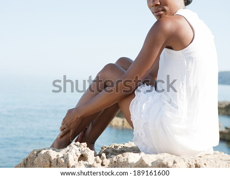 Faceless body view of a young african american black woman sitting down on a natural rock platform high up contemplating the sea during a summer holiday. Healthy relaxing lifestyle. - stock photo