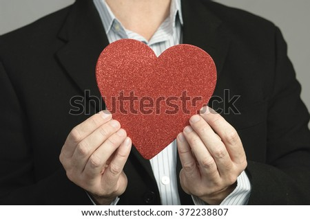 Faceless casual business man holding a Valentine's heart