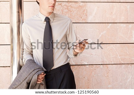 Faceless fashionable businessman wearing an elegant suit and shades, leaning on a modern office building in the city and using a smart phone. - stock photo