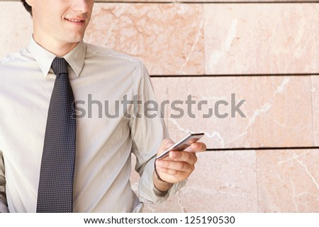 Faceless fashionable businessman wearing an elegant suit, leaning on a modern office building in the city and using a smart phone. - stock photo