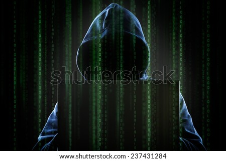Faceless hooded anonymous computer hacker with programming digital code from monitor - stock photo