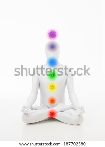 faceless man dressed in white sitting in yoga lotus position with chakra colored graphics - stock photo