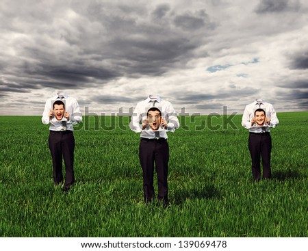 faceless men standing on the green field and holding images with different emotions