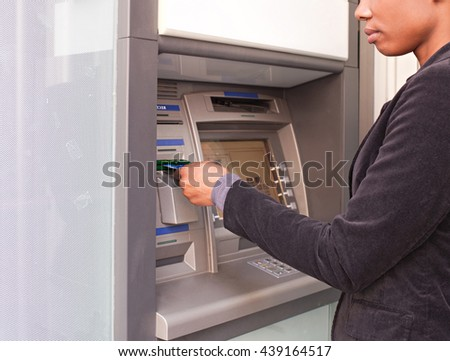 Faceless view of african american business woman using a credit card to withdraw money in a bank cash point in the city, outdoors lifestyle. Professional ethnic woman accessing funds in slick bank.