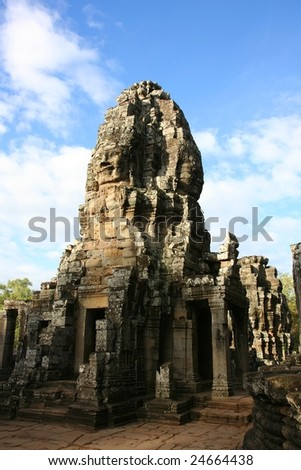 Faces carved in rock at Bayon Temple at Angkor in Cambodia - stock photo
