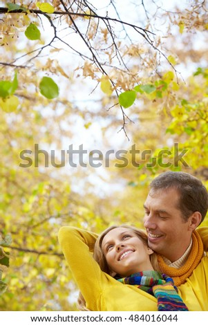 Faces of a couple embracing under autumn tree