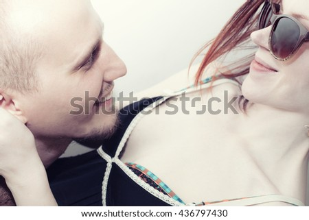Faces of a young kissing man and woman close up - stock photo