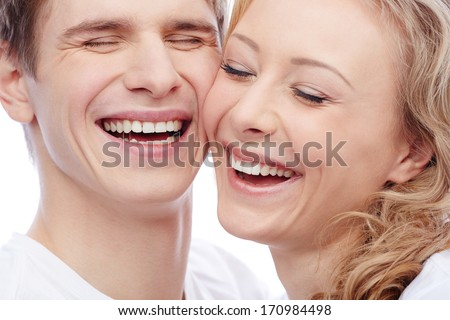 Faces of amorous young couple laughing with closed eyes - stock photo