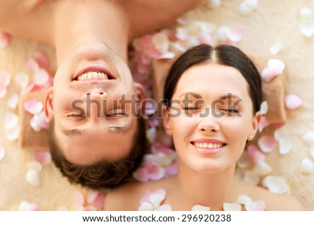 faces of couple in spa salon lying on the massage desks - stock photo