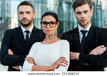 Faces of new business. Three confident business people keeping arms crossed and looking at camera while standing outdoors - stock photo