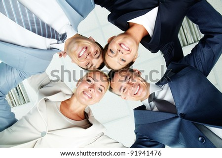 Faces of several successful partners looking at camera with happy smiles - stock photo
