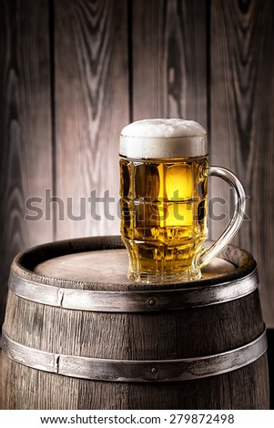 Faceted glass of light beer with a thick foam on an old wooden barrel