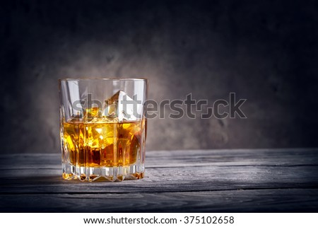Faceted glass of whiskey with ice on dark background - stock photo