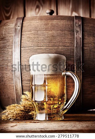 Faceted mug of light beer on a background of the old wooden barrels - stock photo