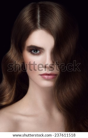 Facial beauty portrait of young girl with chestnut head, big green eyes, pouty lips with natural lipstick on black background - stock photo