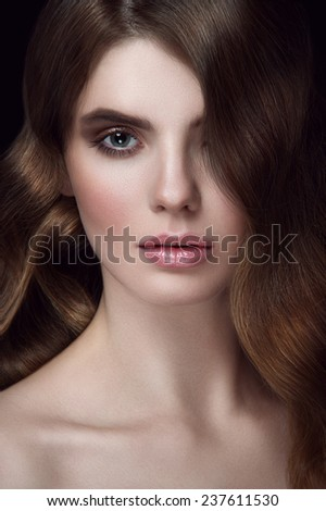 Facial beauty portrait of young girl with chestnut head, big green eyes, pouty lips with natural lipstick, gap in teeth and curls falling on her eye with face turned down - stock photo