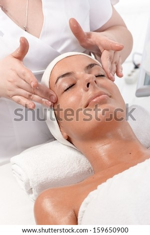 Facial beauty treatment, massage at dayspa, young woman laying relaxed. - stock photo
