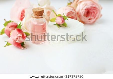 Facial cleanser skincare spa set handmade organic soap white foam rose oil in bottles fresh rose flowers - stock photo
