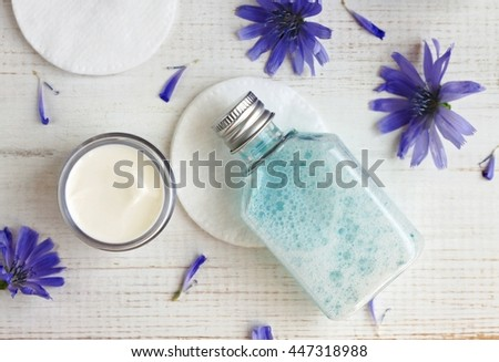 Facial cleansing tonic, white moisturizer cream, cotton pads, blue chicory flowers. Botanical extracts, holistic skincare. - stock photo