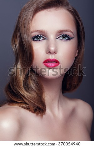 Facial closeup portrait of one caucasian woman with wavy brown hair and bright makeup  - stock photo