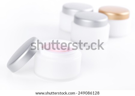 Facial cream in white jar on skincare cosmetic products background - stock photo