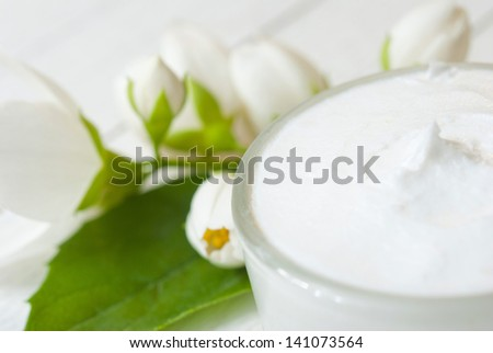 facial cream with jasmine blossom on white wooden table