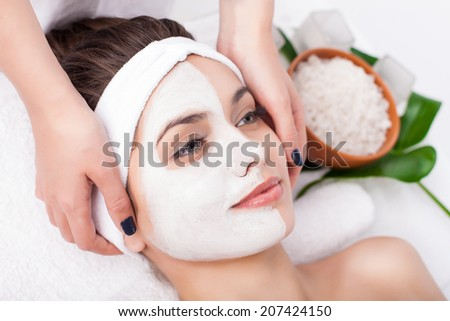 Facial mask of caucasian young female. Spa treatment - stock photo
