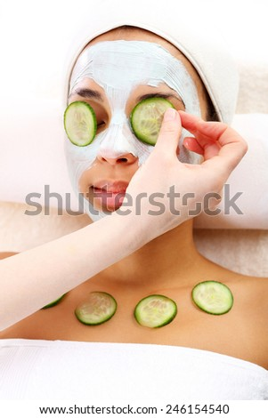 Facial mask, the woman at the beautician. Cosmetic procedure woman's face in the mask mitigating and cucumber slices on eyes  - stock photo