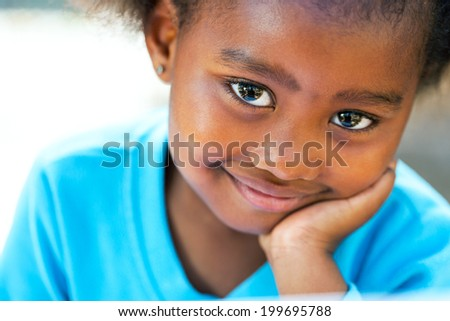 Facial portrait of cute African girl resting cheek on hand. - stock photo