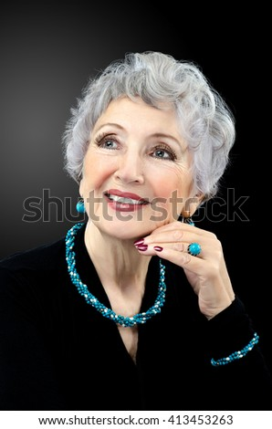 Facial portrait of senior woman wearing turquoise twisted bead necklace, bracelet, ring and earrings. Grey haired spectacular old woman posing on black background. Vertical shot.