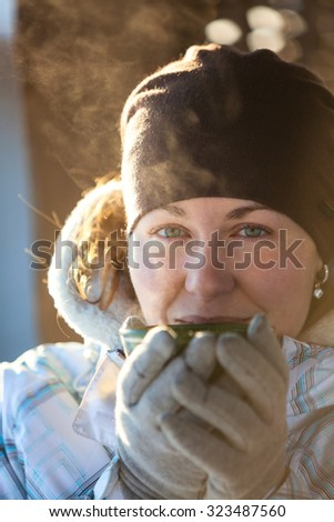 Facial portrait of woman drinking hot tea from mug holding it in hands with mittens, winter - stock photo